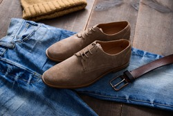 Mans shoes and blue jeans with hat ,belt,on wood background