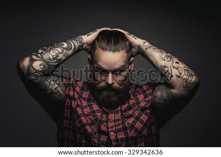 Mans with beard and tattoes on arms holding his head. Isolated on grey background. Stock photo ©