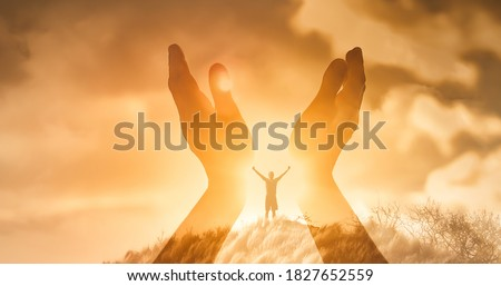 Mans worshiping hands raised up with open palms to the sunset sky. Religion and spirituality belief concept.