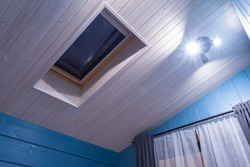 Mansard window in roof. Window in the ceiling of a wooden house. Country house with a skylight. Stargazing window. The walls and ceiling of the room are lined with wood.