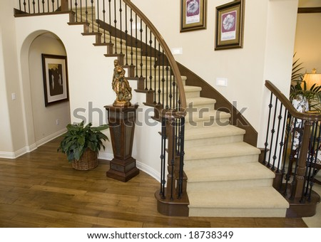 Mansion hallway with modern staircase and luxurious decor.