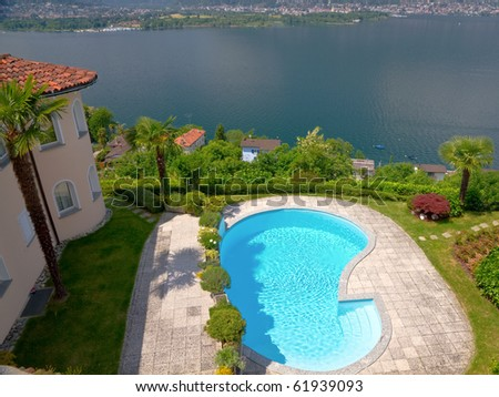 mansion like house with round tower and palm tree an pool resides high over a lake