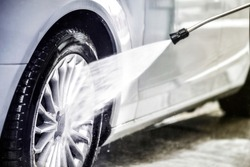 Manual car washing with water jet. Car wash wheel detail. Clean car at wash station.