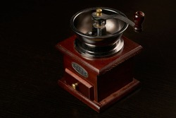 Manual coffee grinder for grinding coffee beans. Black background. Vintage coffee grinder