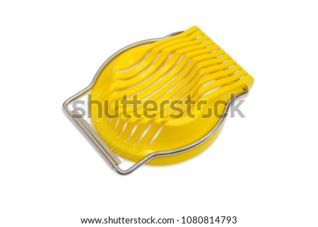 Manual egg slicer with yellow plastic slotted dish and steel plate of wires on a white background