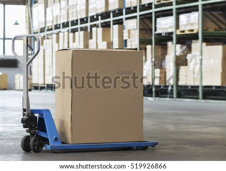 Manual forklift pallet with a big box in a large modern warehouse
