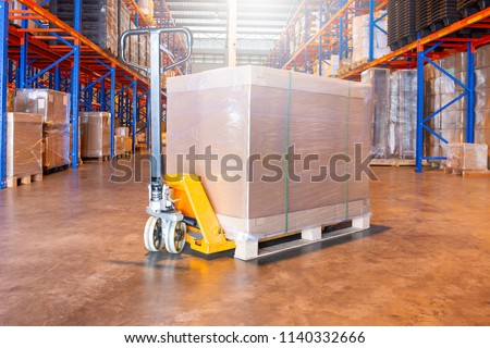 Manual forklift with shipment pallet in large warehouse.