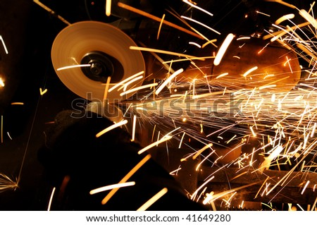 Manual sharpening and cutting of metal by grinding machine - stock photo