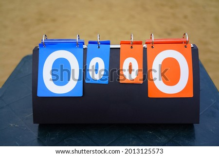 Manual sports scoreboard showing a nil nil score in an outside field Stok fotoğraf ©