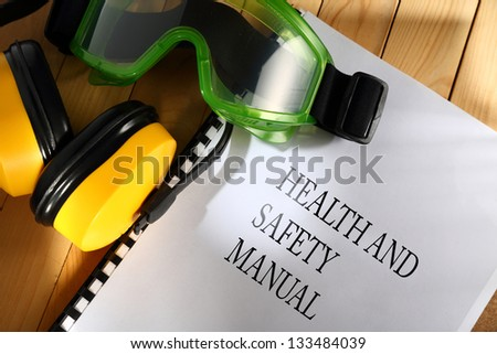 Manual with goggles and earphones on wooden background