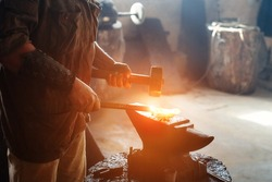 Manual work of a blacksmith in a blacksmith Shop. Hammer blows on the iron billet on the anvil. Forging sword blades is a retro weapon