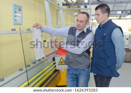 manual worker and businessmen with documents at warehouse