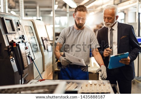 Manual worker and mature engineer checking quality of manufactured components while going through reports in industrial facility.