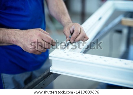 Manual worker assembling hinge on PVC doors and windows. Workshop for aluminum and PVC windows and doors production.