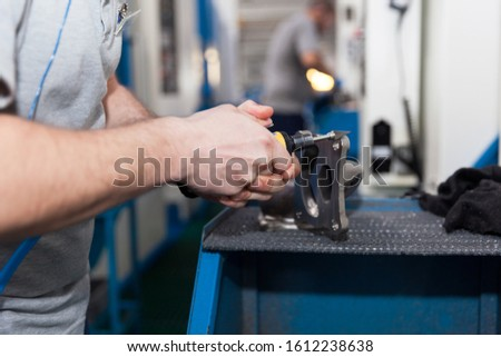 Manual worker at work in the automotive industry factory