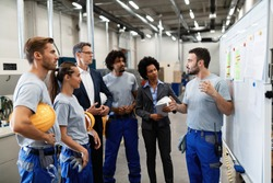 Manual worker communicating with company leaders and his coworkers during business presentation in a factory.