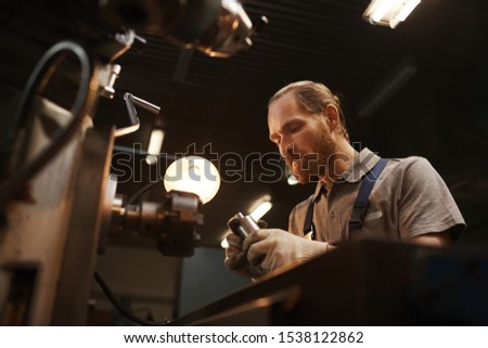 Manual worker concentrating on his work he making metallic details on the lathe in the plant