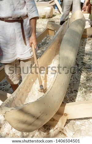 Manual worker craftsman build a boat from wood material tree trunk using special hammer work tool. Hobbies and interests boats woodworking watercraft concept – image