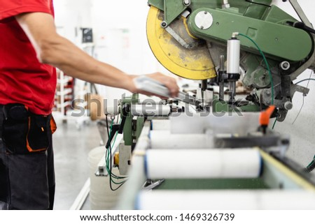 Manual worker cutting aluminum and PVC profiles. Manufacturing jobs. Selective focus. Factory for aluminum and PVC windows and doors production.