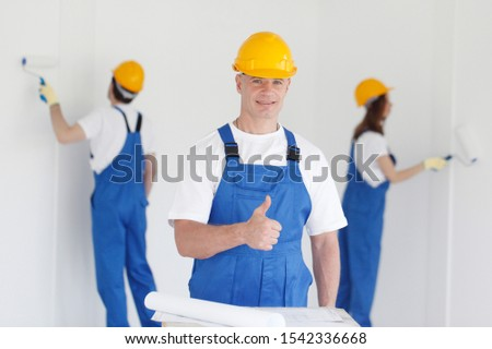 Manual worker gives thumbs up in front of two house painters painting walls