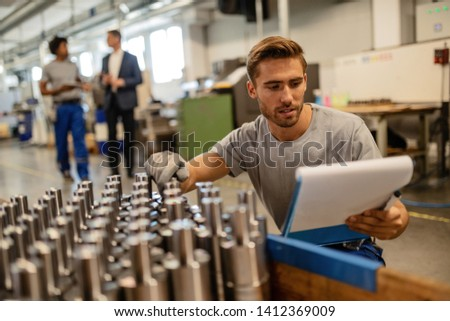 Manual worker going through reports while examining chromed steel rods in a factory.