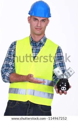 Manual worker holding piggy-bank