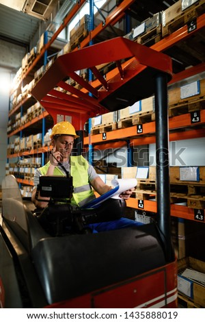 Manual worker in a forklift going through paperwork while working in industrial warehouse.