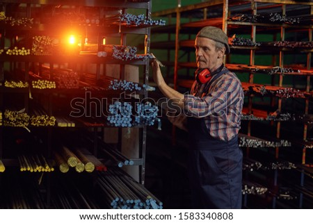 Manual worker in overalls looking at metal pipes on the shelves and using digital tablet in warehouse