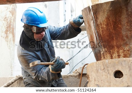 manual worker in protective work wear  beating a metal form by hammer - stock photo