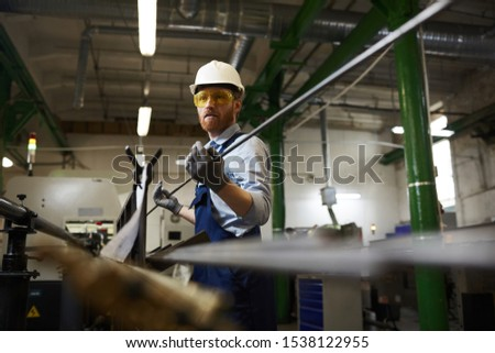 Manual worker in protective workwear and glasses wearing gloves holding iron pipe while working in the factory