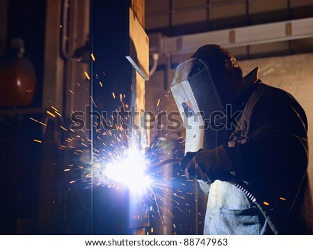 Manual worker in steel factory using welding mask, tools and machinery on metal. Horizontal shape, side view, waist up