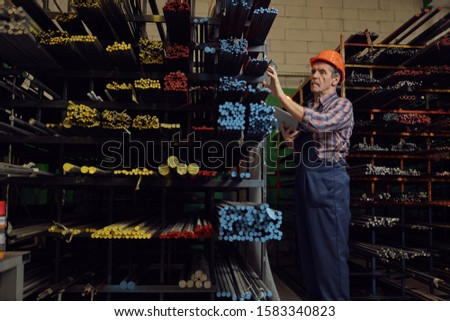 Manual worker in work helmet using digital tablet and checking the metal pipes on the shelves in the factory