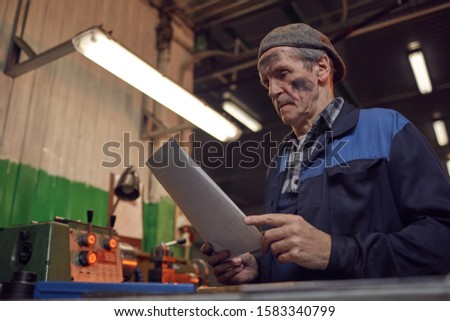 Manual worker in work wear reading the contract while sitting in the plant