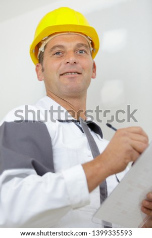 manual worker in yellow hard hat with clipboard