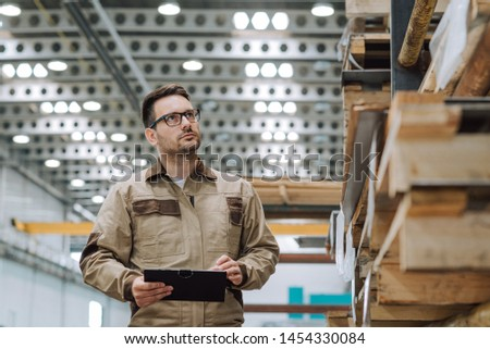 Manual worker looking at shelves in factory warehouse.