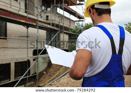 Manual worker on construction site during building inspection.