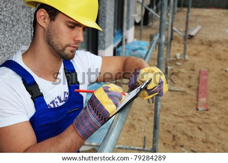 Manual worker on construction site writing on clipboard.