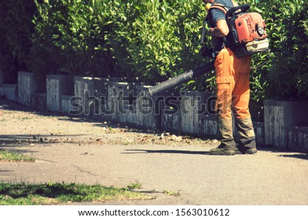 Manual worker on the street, road sweeper using a leaf blower