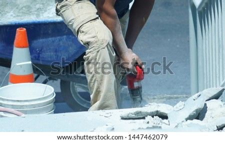 manual worker operating drill to repair the road