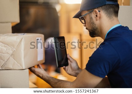 Manual worker preparing for delivery and scanning bar code on package with a digital tablet.