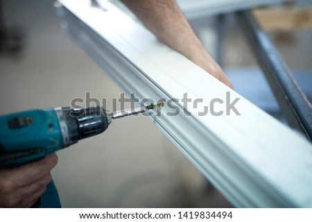 Manual worker screwing pvc window frame in workshop. PVC furniture production.