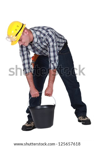 Manual worker trying to lift bucket
