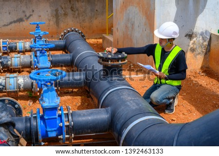 Manual worker turning big valve in industrial plant
