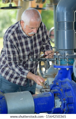 manual worker turning cut-off valve at plant