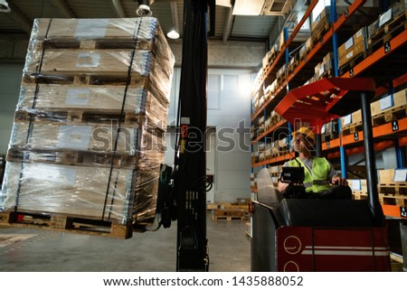 Manual worker using forklift while loading pallets in distribution warehouse.