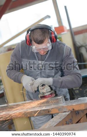 manual worker using grinder on metal in factory