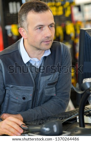 manual worker using laptop in warehouse
