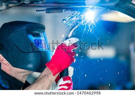 Manual worker wearing protection mask welding metal in car service