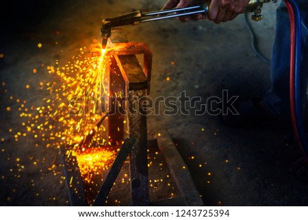 Manual worker welding iron while working in a workshop