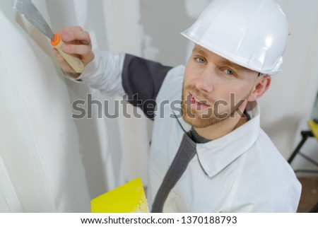 manual worker with wall plastering tools inside a house #1370188793